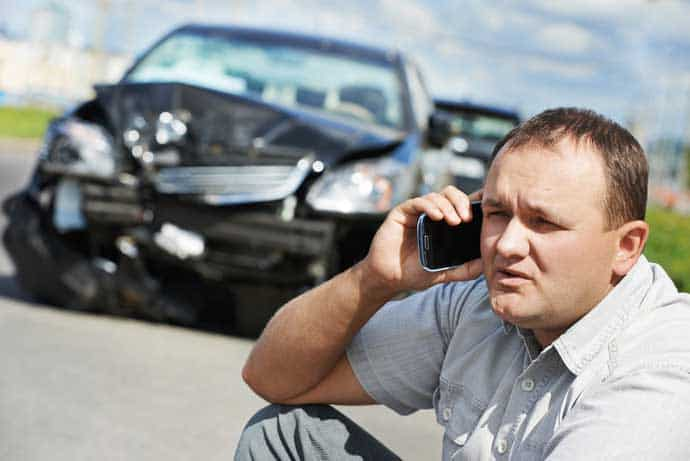 Upset man on cell phone after car crash with an uninsured motorist
